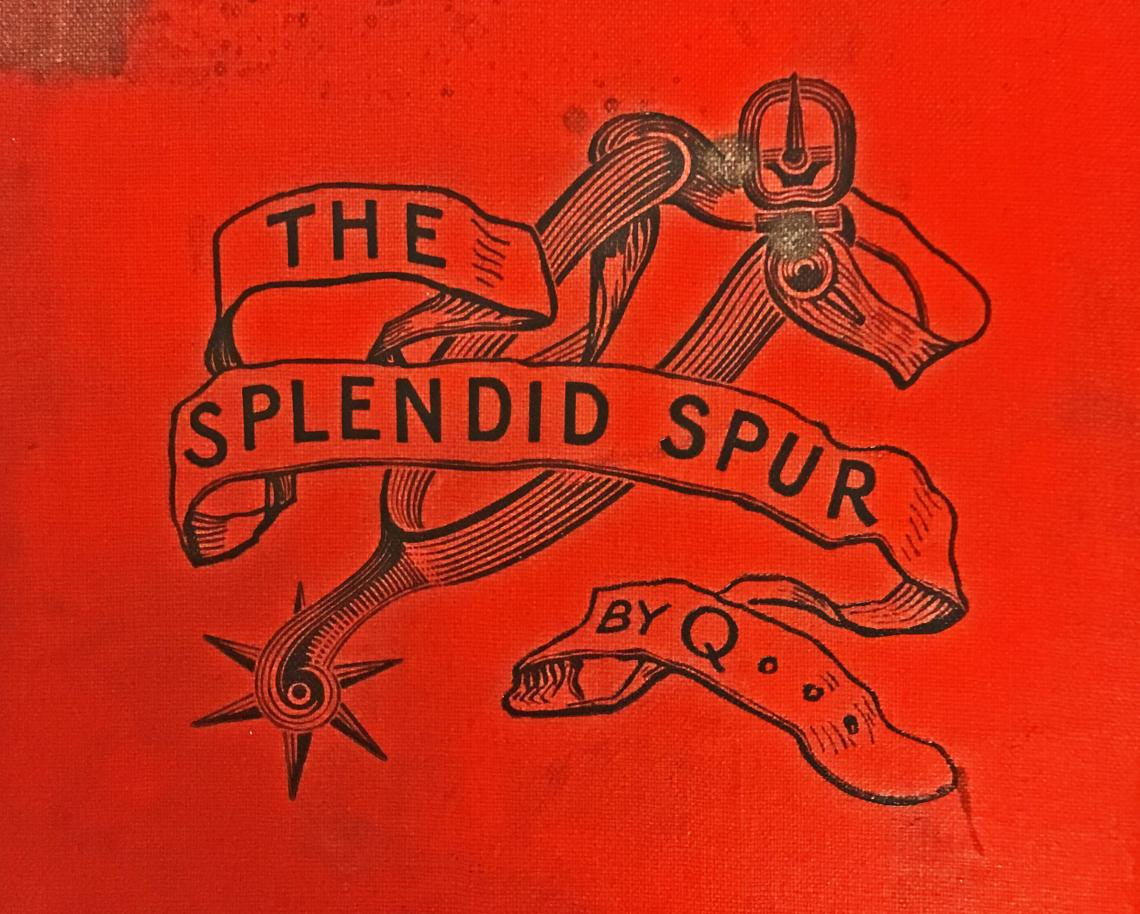 Detail from the cover of The Splendid Spur showing a spur and a strap which bears the title of the book